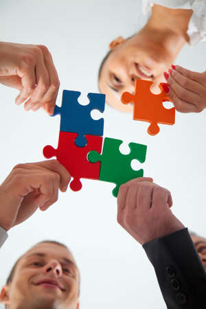 working group: Group of business people assembling jigsaw puzzle and represent team support and help concept in office.