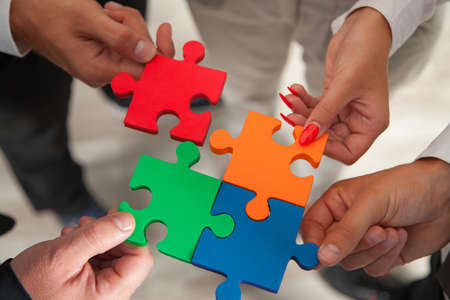 Group of business people assembling jigsaw puzzle and represent team support and help concept in office. Stock fotó - 37470313