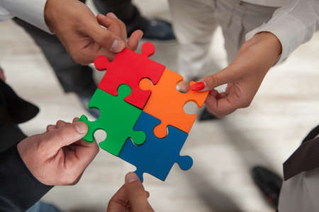 group solution: Group of business people assembling jigsaw puzzle and represent team support and help concept in office.