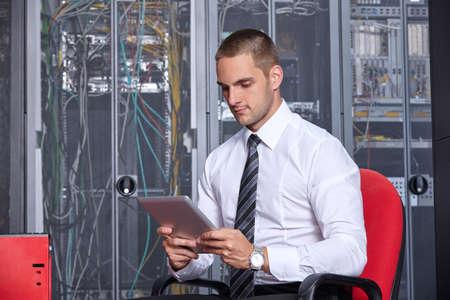isp: businessman hand using tablet computer in modern server room