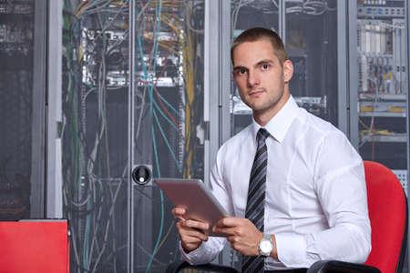 businessman hand using tablet computer in modern server room