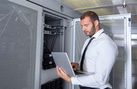 server hardware: business man engeneer in modern datacenter server room