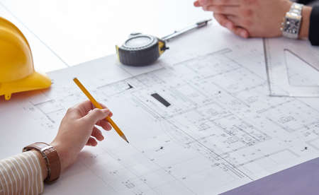 architect tools: Close Up Of Two Architects Discussing Plan Together At Desk With Blueprints Stock Photo