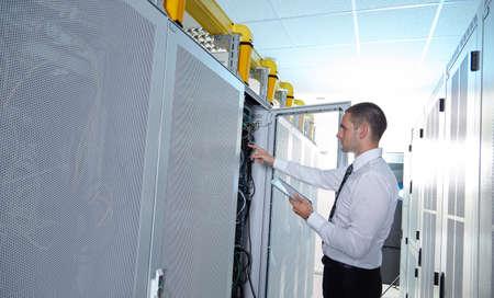 network server: businessman hand using tablet computer in modern server room