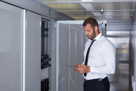 data center data centre: businessman hand using tablet computer in modern server room