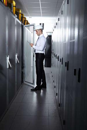 server room: businessman hand using tablet computer in modern server room