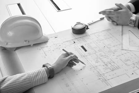 Close Up Of Two Architects Discussing Plan Together At Desk With Blueprints Фото со стока
