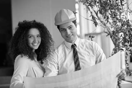 construction project: Young Architects in office looking at construction project Stock Photo
