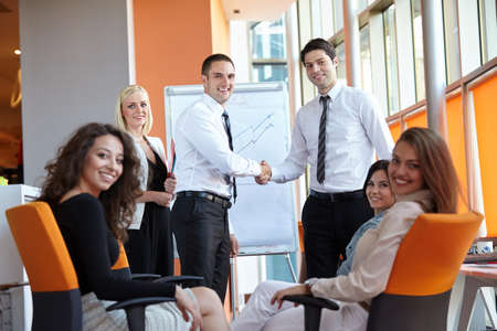 business women: businessman shaking hands to seal a deal with his partner and colleagues in a modern office