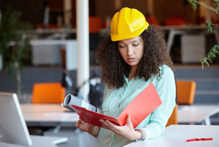 architect: Woman Architect at work site with blueprints Stock Photo