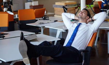 relajado: Hombre de negocios Relaxed que trabaja con un ordenador portátil en su oficina