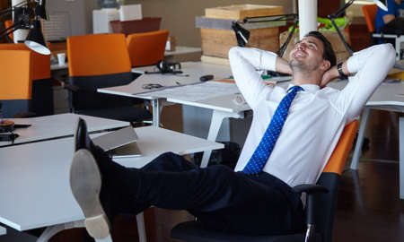 relaxed: Relaxed businessman working with a laptop in his office
