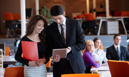 show business: busy business people working on tablet Stock Photo