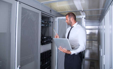it engeneer businessman with thin modern aluminium laptop in network server room Stock fotó - 47402450