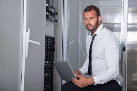 server room: it engeneer businessman with thin modern aluminium laptop in network server room