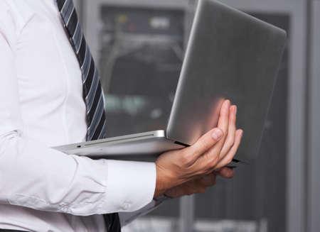 isp: it engeneer businessman with thin modern aluminium laptop in network server room