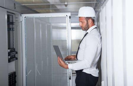 computer centre: de ingeniero empresario con fina aluminio moderna port�til en la sala de servidor de red