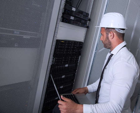 business services: it engeneer businessman with thin modern aluminium laptop in network server room