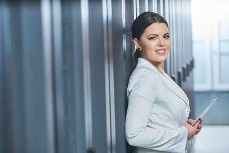 female technician working on server maintenance in white server room