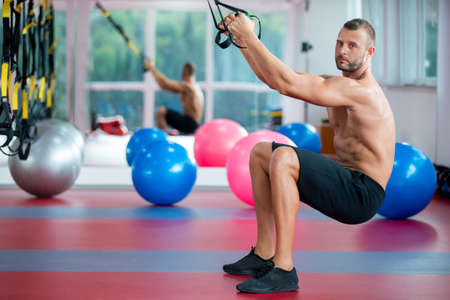 guy doing push ups training arms with trx fitness straps in the gym Concept workout healthy lifestyle sport Banque d'images