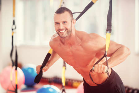 guy doing push ups training arms with trx fitness straps in the gym Concept workout healthy lifestyle sport Stock Photo