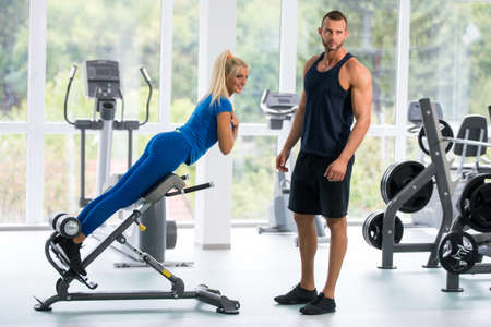 Attractive young sports people are talking and smiling while lying in gym