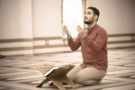 Religious muslim man praying inside the mosque 스톡 콘텐츠