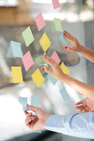 business, startup, planning, management and people concept - happy creative team writing on stickers at office glass board