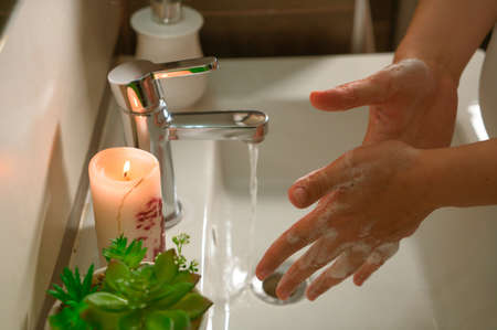 Washing hands with soap and hot water at home bathroom sink women cleansing hand hygiene for coronavirus outbreak prevention. Corona Virus pandemic protection by washing hands frequently.