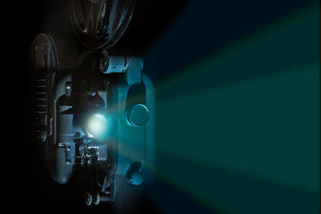 Vintage 8 mm filmprojector in een donkere ruimte met rollen en lichtstraal
