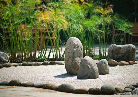 Een rustige Zen rotstuin met papyrusplant Stockfoto
