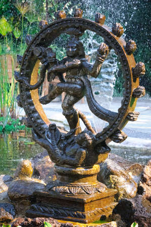 vedic: Bronze statue of indian goddess Shiva Nataraja - Lord of Dance in a fountain with papyrus plant