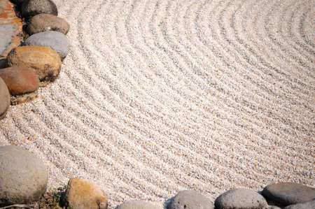 A Zen garden makes symbolic representations of natural landscapes using stone arrangements, white sand raked that symbolizes sea, ocean, rivers or lakes. photo