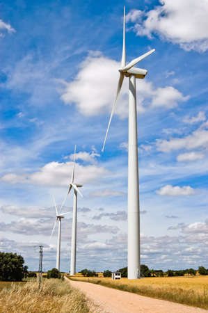source: Path of modern wind turbines in a country road with blue sky and clouds. With eco friendly technology mechanical energy is used to produce electricity, also called wind generator or wind charger.
