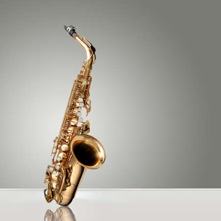 Alto Saxophone woodwind instrument over gray neutral background Stock Photo