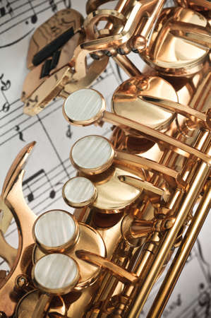 saxophone: Alto Saxophone main, palm left hand keys & spatula  table keys closeup with score notes in background