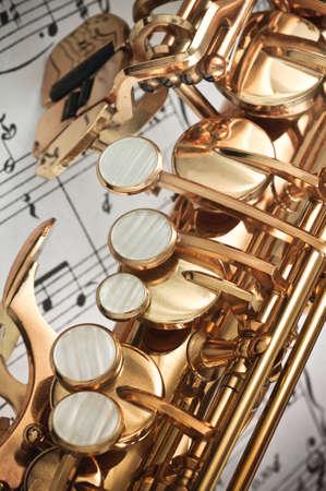 saxofon: Saxofón principal, palma de la mano izquierda las llaves de manos y una espátula  table primer plano las teclas con las notas puntuación en el fondo
