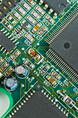 PCB Closeup of green electronic circuit board and components photo
