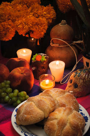 Offering as part of the celebration of the day of the dead in Mexico with bread Pan de Muerto&uml, chocolate and amaranto skulls and flowery in background
