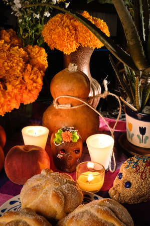 Offering as part of the celebration of the day of the dead  Dia de Muertos  in Mexico with bread  Pan de Muerto  chocolate and amaranto skulls and flowery in background  Stok Fotoğraf