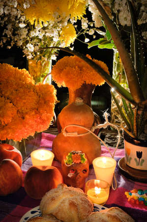 Offering as part of the celebration of the day of the dead  Dia de Muertos  in Mexico with bread  Pan de Muerto  chocolate skull and flowery in background