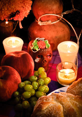 altar: Offering as part of the celebration of the day of the dead  Dia de Muertos  in Mexico with bread  Pan de Muerto  chocolate skull and flowery in background