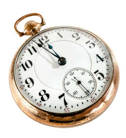 reloj antiguo: Antiguo reloj de bolsillo de oro que muestra unos minutos para la medianoche aislado en fondo blanco concepto de tiempo, del pasado o del plazo Foto de archivo