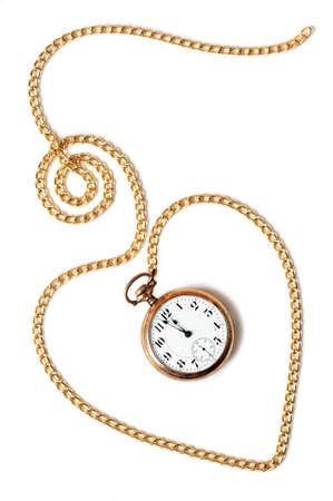 Hart pad gemaakt met een gouden ketting en een zakhorloge binnen met een paar minuten voor middernacht, geïsoleerd op witte achtergrond Concept van duurzaamheid van de liefde in de tijd, het verleden of de termijn Stockfoto