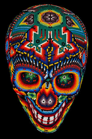 Colorful Beaded Skull from mexican traditional huichol bead art, symbol of the day of the dead,  isolated on black Standard-Bild