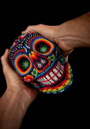 Beaded Skull with hands  Surprised  - Colorful skull from mexican traditional huichol bead art, symbol of the day of the dead  Stock Photo - 14591950