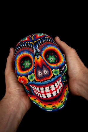 mexican folklore: Smiling death at your hands - Colorful skull from mexican traditional huichol bead art