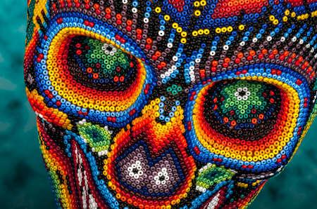 죽음의 날의 멕시코 전통 huichol 구슬 예술, 기호에서 다채로운 구슬로 장식 된 해골
