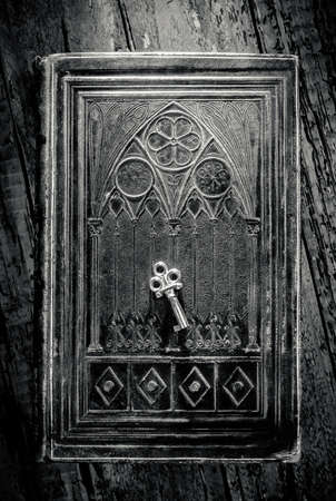Old metal key lying on a decorated ancient book in black and white photo