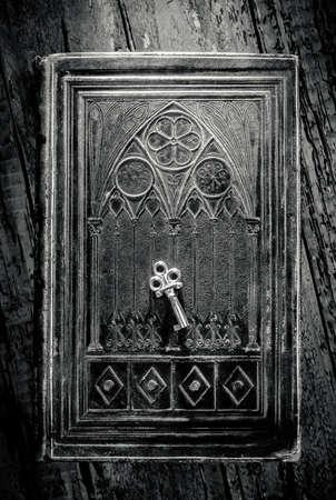Oude metalen sleutel liggend op een versierde oude boek in zwart en wit